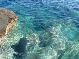 The crystal clear waters of the Aegean Sea @Kamari Beach, Santorini, Greece